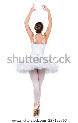 Young beautiful ballet dancer is posing on a studio background.