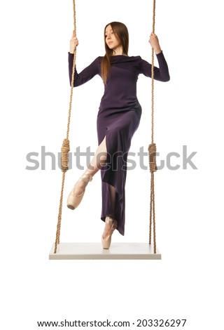 young beautiful ballet dancer posing on swing