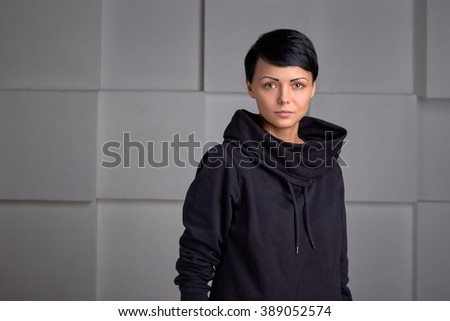 Young  beautiful black sport wear girl with short hair style  on white cube background. Model posing. - stock photo