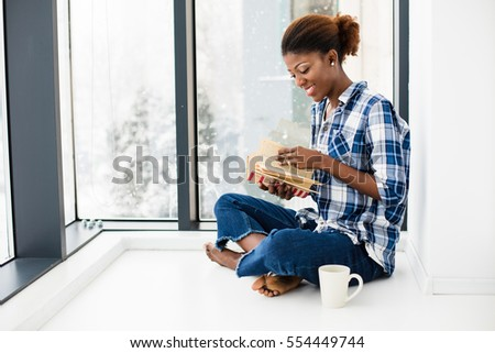 young beautiful black woman lying on the floor and reading a book next to big windows with natural light