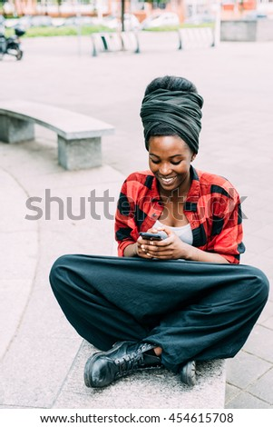 Young beautiful black woman sitting leg crossed on a bench, tapping and looking at the screen of a smart phone hand hold, smiling - technology, social network, happiness concept - stock photo