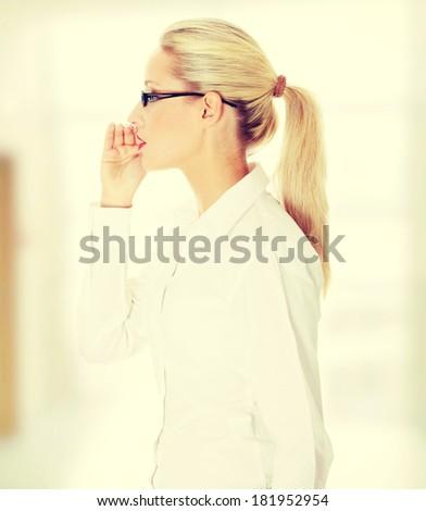 Young beautiful blond businesswoman talking gossip - stock photo