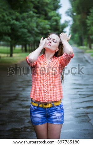 Young beautiful blond caucasian girl in shorts and shirt walking in the park in the summer warm rain barefoot through the puddles. Have fun and enjoy. Falling rain. Raindrops. Wet clothes - stock photo