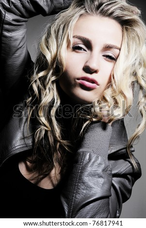Young beautiful blond girl posing in gray jacket.