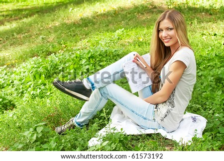 Young beautiful blond girl sitting on the grass