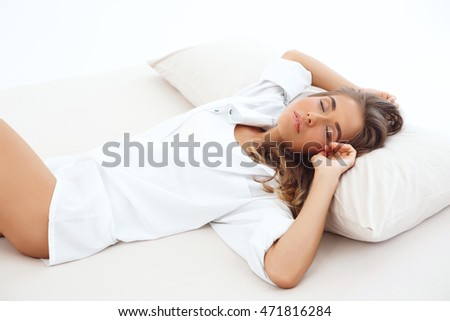Young beautiful blond girl sleeping on bed early in morning.