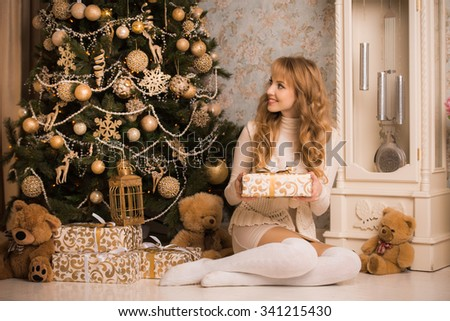 Young beautiful blond girl, woman in a beautiful room with a Christmas tree, a Christmas tree, a girl with gifts, gold tree, golden hair, happy woman new year, sitting in the armchair - stock photo