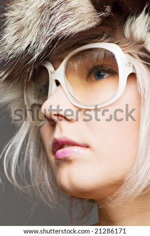 young beautiful blond in fur hat and sunglasses over grey background