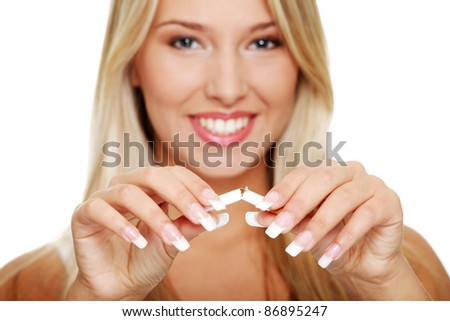 Young beautiful blond smiling woman breaking cigarette, isolated on white - stock photo
