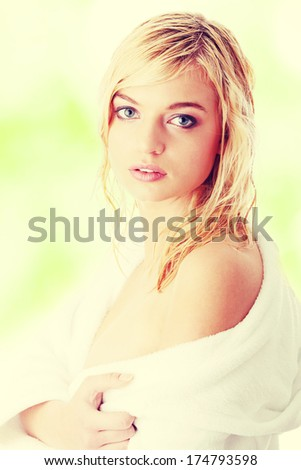 Young beautiful blond teen woman dressed in white bathrobe  - stock photo