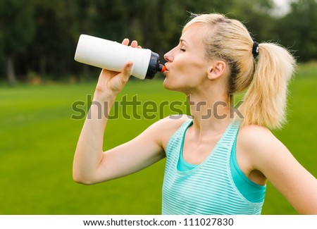 Young beautiful blond woman drinking water at summer green park - stock photo
