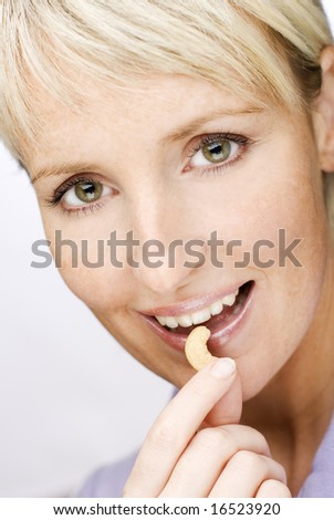 young beautiful blond woman eating cashew nuts close up - stock photo