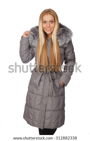 Young beautiful blond woman in a long gray coat with fur collar - stock photo