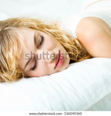 Young beautiful blond woman sleeping on bed - stock photo