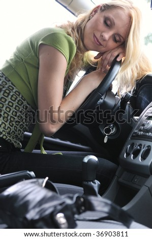 Young beautiful blond woman sleeps in car on steering wheel - detail portrait - stock photo