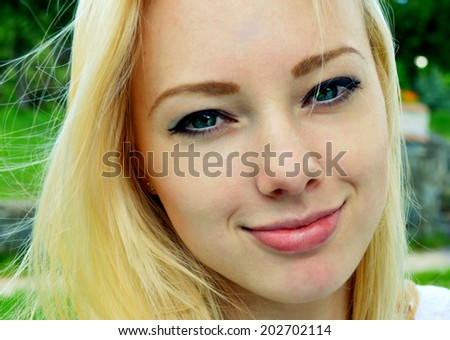Young beautiful blond woman with long hair smiling mischievously