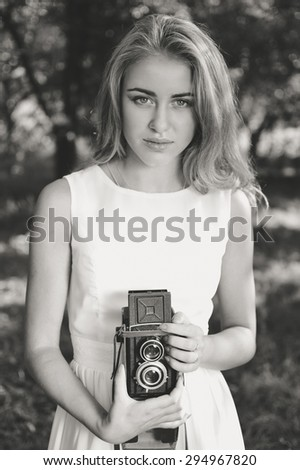 Young beautiful blond woman with retro camera black and white portrait in nature background - stock photo