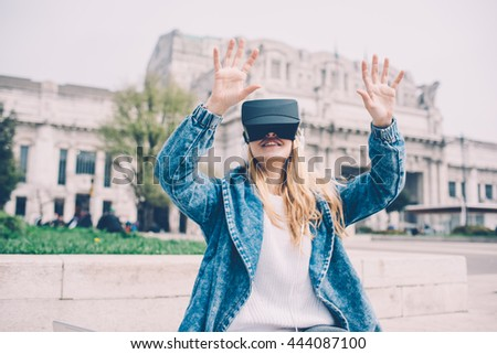 Young beautiful blonde caucasian business woman sitting using 3D viewer - futuristic, multitasking, technology concept - stock photo