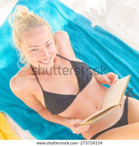Young beautiful blonde caucasian woman in black bikini enjoying reading book on the beach while sunbathing. - stock photo