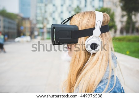 Young beautiful blonde caucasian woman sitting using 3D viewer - futuristic, multitasking, technology concept - stock photo