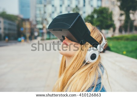 Young beautiful blonde caucasian woman sitting using 3D viewer looking up - futuristic, multitasking, technology concept