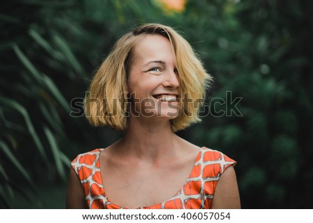 young beautiful blonde girl against the tropical palm trees. beautiful girl with an attractive smile and glowing eyes. emotional portrait of fashion portrait of pretty young hipster blonde. woman. - stock photo