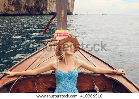 Young beautiful blonde girl cruising on retro wood boat by Andaman sea and behind her you can see Ko Phi Phi Lee Island in full glory. Dressed in beautiful blue dress and wearing straw hat. - stock photo
