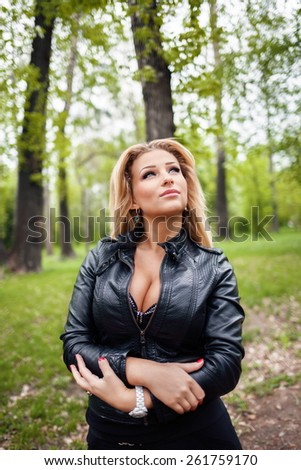 Young beautiful blonde girl in a leather jacket standing in the park. - stock photo