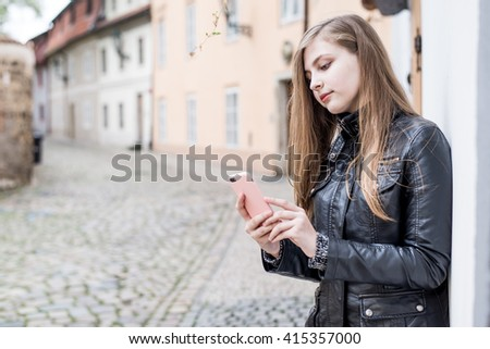 young beautiful, blonde girl in Old Town playing with her phone and making self portrait   - stock photo