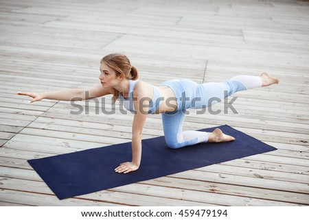 Young beautiful blonde girl practicing yoga outside.