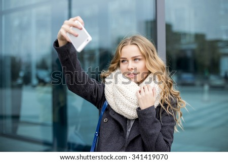 Young beautiful blonde girl taking selfie with mobile phone - stock photo