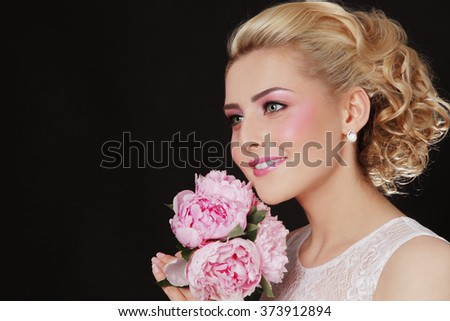 Young beautiful blonde happy bride with stylish prom hairdo and bridal bouquet