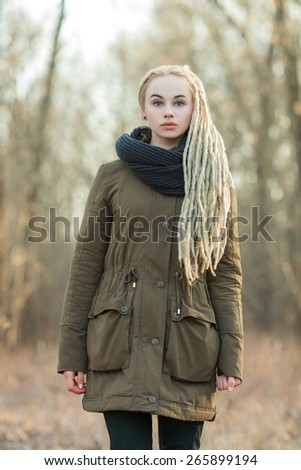 Young beautiful blonde hipster woman in scarf and parka with dreadlocks hairstyle posing on a blurry forest background - stock photo