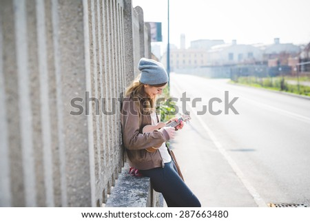 young beautiful blonde hipster woman in the city road with ukulele