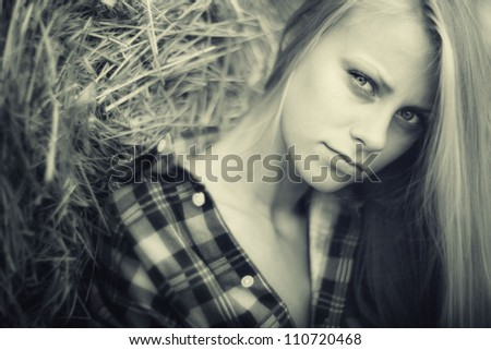 young beautiful blonde in the hay in an outdoor