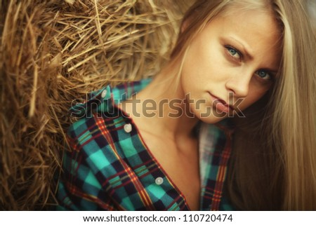 young beautiful blonde in the hay in an outdoor - stock photo