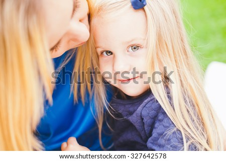 Young beautiful blonde mother and her cute little daughter smiling and relaxing in park in summer. Both wear blue dresses. Bow in daughter hair. Little girl is shy and smiles and mother coo with her - stock photo
