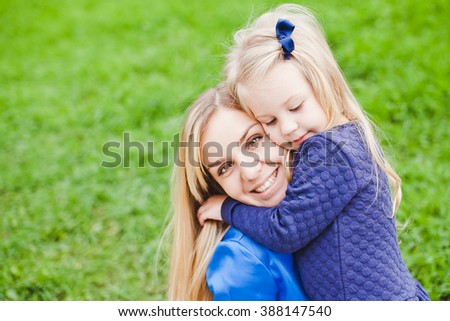 Young beautiful blonde mother and her shy cute little daughter hug smiling and relaxing in park in summer. Both blonde in blue dresses. Concept of happiness in parenthood and family. Copy space - stock photo