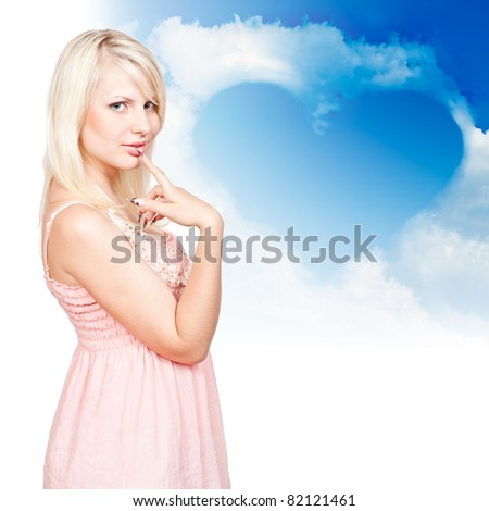 young beautiful blonde on a background of clouds in the shape of a heart