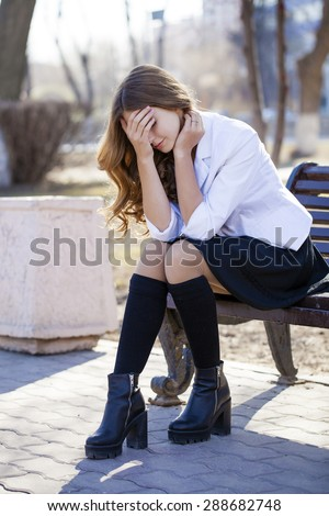 Young beautiful blonde schoolgirl sitting on a bench, spring street - stock photo