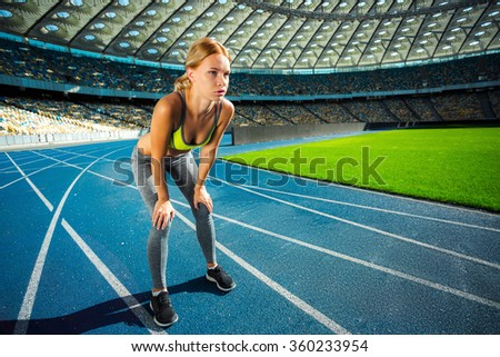 Young beautiful blonde sportswoman resting after running on racetrack outdoors. Fit woman is at large nice modern stadium