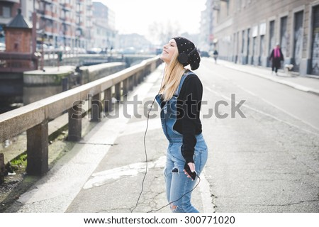 young beautiful blonde straight hair woman in the city with headphones listening to music - freedom, emancipation concepts