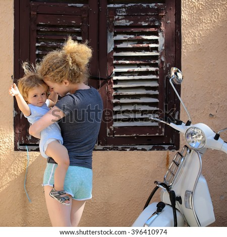 Young beautiful blonde woman holding little baby boy child in hands standing near house with brown window and white motor bike urban transportation sunny day outdoor, square picture - stock photo