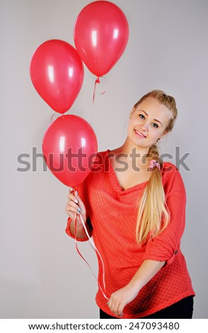 young beautiful blonde woman holding three balloons