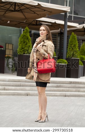 Young beautiful blonde woman in beige short coat posing outdoors in spring street - stock photo