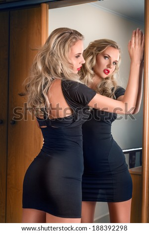 Young beautiful blonde woman in black mini dress posing near mirror - stock photo