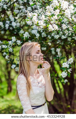 Young beautiful blonde woman in blooming garden. Bride. Closed eyes. - stock photo