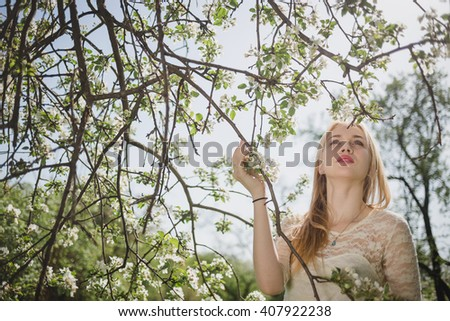 Young beautiful blonde woman in blooming garden. Bride. Delicate girl enjoys spring nature - stock photo