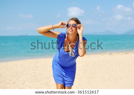 Young beautiful blonde woman in blue dress posing outdoors in sunny weather