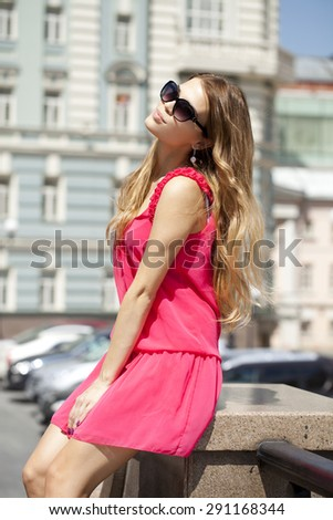 Young beautiful blonde woman in sunglasses, against the blue sky on a sunny day - stock photo